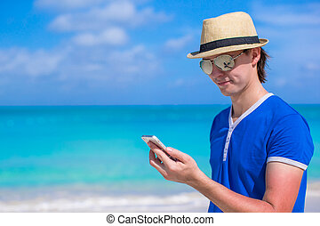 Young businessman with his phone on beach vacation - Young...