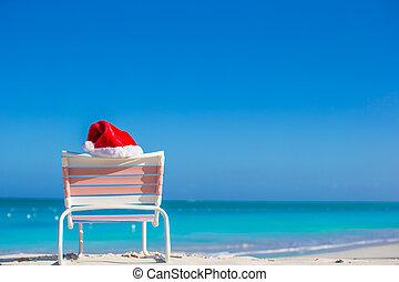 Red Santa hat on chair longue at sea shore - Closeup santa...