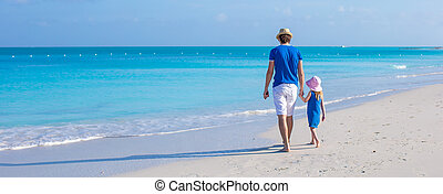 Little adorable girl and her father walking along the sea -...