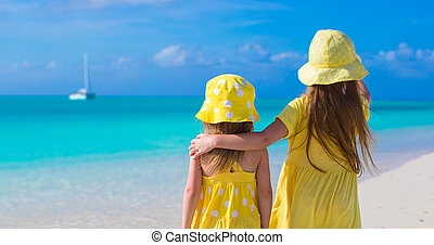 Back view of two adorable little girls on caribbean vacation...
