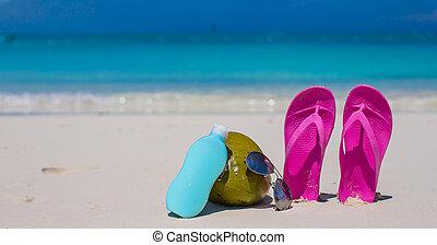 Flip flops, coconut and suncream on white sand - Flip flops...