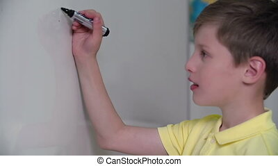 Doing Sums - Close up of school boy called to the whiteboard...