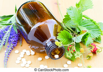 Natural medicine - brown glass bottle, pills and wild...