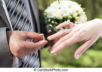 Wedding day. Groom putting ring on bride's finger