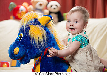 Baby on a rocking horse - 10 months old baby girl riding...