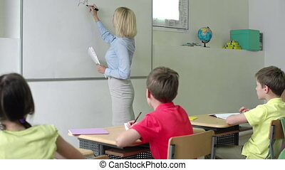 At the Lesson - Over shoulder shot of pupils at desks...
