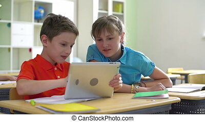 Millenials - Close up of two school friends surfing the net...