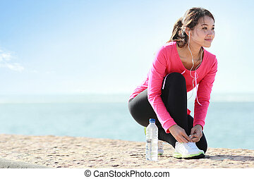 Tying shoelaces on the beach - Girl tying shoelaces while...