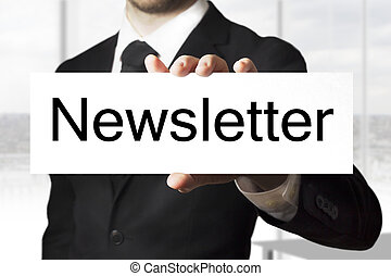 businessman holding sign newsletter - businessman in black...