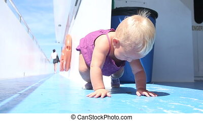 child tries to get up on ship deck