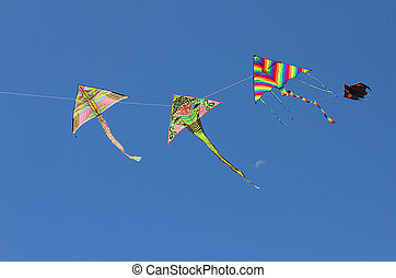 four beautiful kites flying in the blue sky in summer
