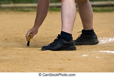 Home Plate Umpire cleans off the plate before the start of...