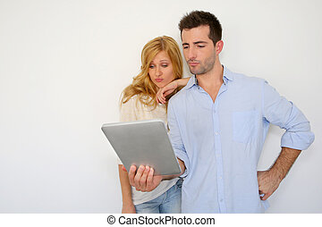 Couple looking at tablet screen with puzzled look