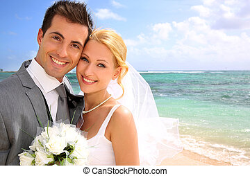 Portrait of beautiful bride and groom at the beach