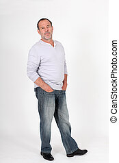 Senior man standing on white background with hands in pocket