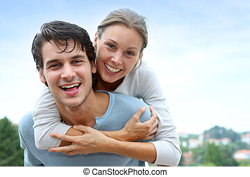 Man giving piggyback ride to girlfriend outside