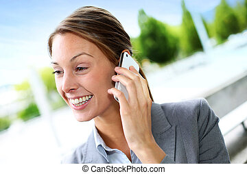 Profile view of cheerful businesswoman talking on cellphone