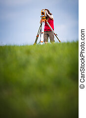 Young, female land surveyor at work - using the t
