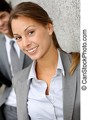 Closeup of businesswoman with people in background