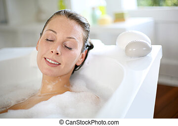 Woman relaxing in bathtub with eyes closed
