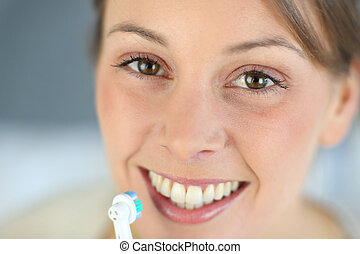 Closeup on womans toothy smile brushing her teeth