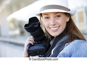 Beautiful woman photographer holding photo camera