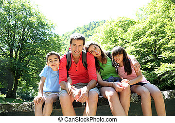 Portrait of family sitting on a bridge in forest