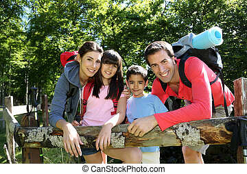 Family on a hiking day resting along fence