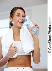 Cheerful fitness girl drinking water after exercising