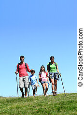 Family of four hiking in the mountain by sunny day