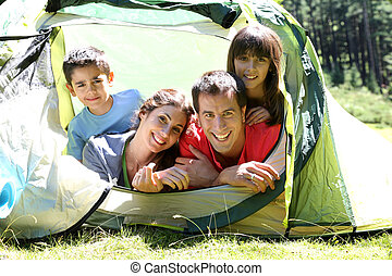 Portrait of family laying in camp tent