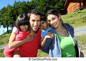 Parents and children standing in front of mountain log cabin