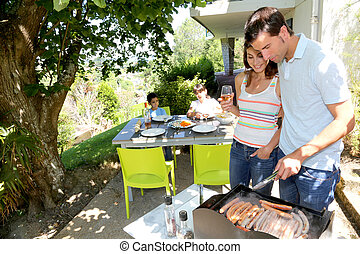 Family cooking meat on barbecue grill