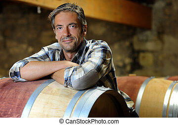 Smiling winemaker leaning on wine barrel in winery