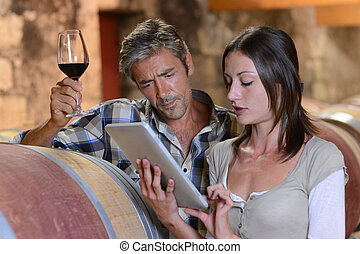 Winemakers in cellar using electronic tablet to control wine...
