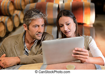 Winemakers in cellar controlling wine market prices on...