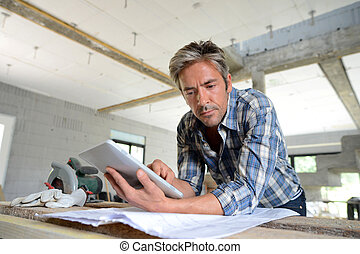 Entrepreneur in house under construction checking plan