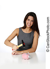 Young woman ready to break piggy bank with hammer