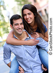 Cheerful young man carrying girlfriend on his back