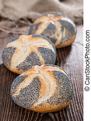 Poppyseed Buns on an old dark wooden table detailed close-up...