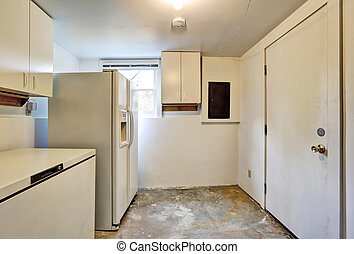 Old ugly room in house basement with white cabinets, old...