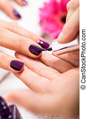 Woman having a nail manicure in a beauty salon with a...