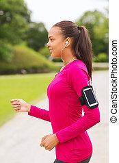 smiling young woman running outdoors - sport, fitness,...