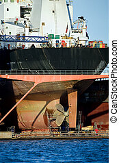 container ship in dry dock - freighter in dry dock with work...