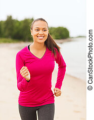 smiling woman running on track outdoors - fitness, sport,...