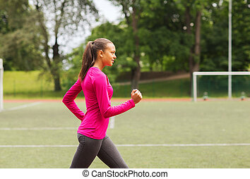 smiling young woman running on track outdoors - fitness,...