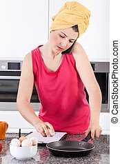 Busy woman making scrambled eggs in the morning