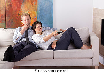 Couple relaxing after long day in front of tv