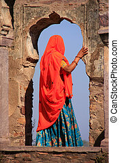 Indian woman in colorful sari standing in the arch,...