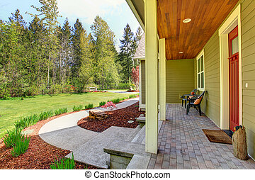 Countryside house exterior. View of entrance porch and curb...